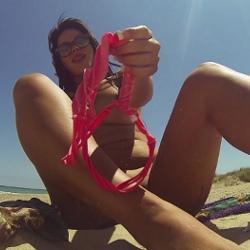 Tania se pajea en una playa nudista rodeada de mirones